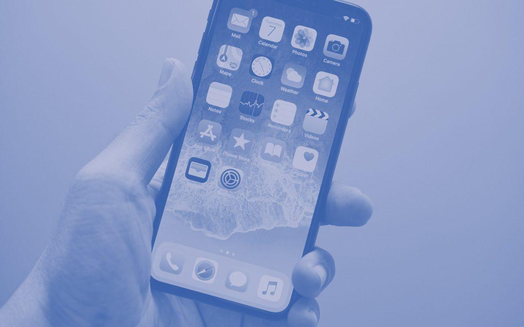 Cellulare tenuto in mano con lo schermo acceso